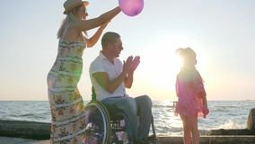 Invalid, pregnant wife and daughter have a good time with colorful air balloons, family with child. Disabled husband on wheelchair with loved ones pregnant wife stock footage