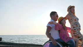 Invalid at summer, family play together on background blue sky, little girl sitting on daddy in wheelchair with. Outstretched arms in backlight, disabled man stock video
