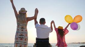 Invalid with wife and daughter raise their hands up with colorful air balloons near sea, family with child