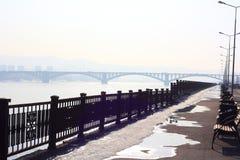 Invallning av floden Yeniseiet River Bänkar längs trottoaren Svart mönstrat staket längs stranden På horisonten Arkivfoto