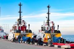 Invallning i porten med fiskare och förtöjde skepp royaltyfria foton