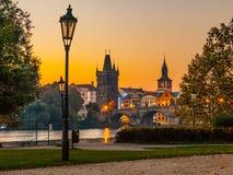 Invallning med den gamla lampan i gammal stad av Prague med den Charles Bridge och Vltava floden tidig förlorad morgon för dimma  Royaltyfri Foto