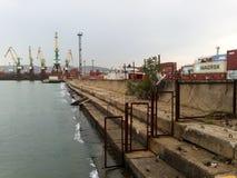 Invallning nära den industriella porten var den kranar anslutade laddade klara shipen för port till Arkivfoton