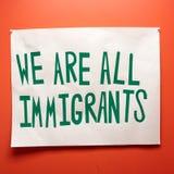 Invandrare och invandringtecken med politiska dämpade toner arkivbild