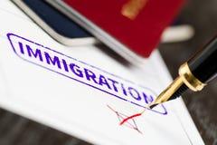 Invandringapplikationen vägrade, stänger sig upp skott av en form, pass och pennan Arkivfoto