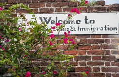 Invandringtecken på en gammal tegelstenvägg Arkivbild