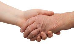 Invecchiamento - stretta di mano fra giovane e vecchio Immagini Stock Libere da Diritti