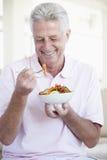 invecchiato mangiando l'insalata della metà dell'uomo Fotografia Stock