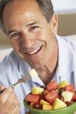 invecchiato mangiando l'insalata della metà dell'uomo della frutta fresca Fotografia Stock Libera da Diritti