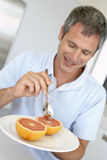 invecchiato mangiando la metà fresca dell'uomo del pompelmo Fotografie Stock