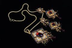 Invecklade indiska guld- smycken på svart bakgrund Arkivfoton
