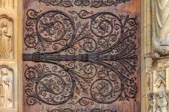 Invecklat arbete för smidesjärntappningsnirkel på dörrgångjärnen av Notre Dame de Paris Cathedral i Paris Frankrike falska metall arkivfoton