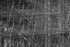 Invecklat material till byggnadsställning som består av många poler och stöttor inom en historisk byggnad som är svartvit royaltyfri bild