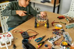 Free Invent. Close Up Of A Boy Using Screwdriver While Fixing Bolts On A Robot Vehicle. Smart Kids And STEM Education. Stock Image - 175924621