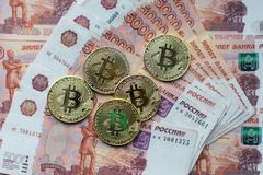 Inventa o bitcoin, mentira em uma conta de 5000 mil rublos As cédulas são espalhadas para fora na tabela em uma ordem livre Fotografia de Stock Royalty Free