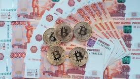 Inventa o bitcoin, mentira em uma conta de 5000 mil rublos As cédulas são espalhadas para fora na tabela em uma ordem livre Foto de Stock