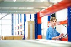 Inventaire de contrôle de femme d'affaires dans un entrepôt Photos stock