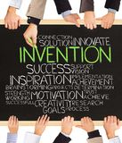 Invention. Photo of business hands holding blackboard and writing INVENTION Stock Photos