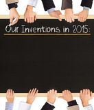 Inventions list. Photo of business hands holding blackboard and writing Our Inventions for 2015 Royalty Free Stock Photo