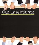 Inventions list. Photo of business hands holding blackboard and writing Our Inventions Royalty Free Stock Image