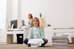 Inventive active child holding some sheets of paper. Calmness of the workplace. Cute sincere hilarious girl sitting on the floor in the office and thinking about Royalty Free Stock Photo