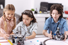 Inventive children testing technologies at school. Sharing opinions. Skillful lively positive pupils sitting at school and enjoying science class while Royalty Free Stock Photos