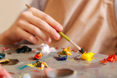 Inventive kid mixing colors in the art studio. Creating new pallet. Pleasant skilled inventive child sitting at school and painting while mixing colors Royalty Free Stock Image