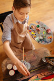 Inventive little boy painting and relaxing at school Stock Images