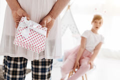 Inventive nice dad greeting his child on her birthday. I got something for you. Cute admirable clever father hiding a gift behind his back and making a surprise Stock Photo