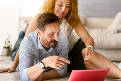 Inventive positive couple working together at home. Full of new ideas. Attentive creative friendly couple sitting at home on the floor and looking at the laptop Royalty Free Stock Image