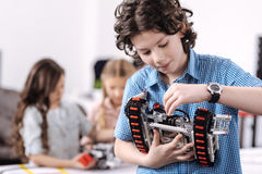 Inventive pupil representing science project at school. Taking part in science progress. Delighted cheerful concentrated boy standing at school and holding robot Stock Photography