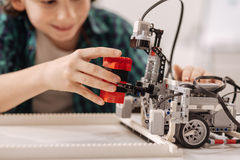 Inventive teen kid constructing robot in the studio. Time of tech invention . Skilled lively smiling boy sitting in the studio while studying and constructing Royalty Free Stock Image