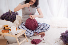 Inventive woman using ball of wool at home. Full of positivity. Involved gifted young woman knitting and enjoying weekend while expressing joy and using ball of Stock Photo