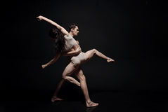 Inventive young dance couple taking part in the art performance. Forming a single whole. Creative inspired masterful performers performing in the studio and Royalty Free Stock Images