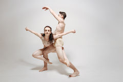Inventive young dancers performing in the white colored studio. Full of creative ideas. Gifted inventive flexile dancers dancing in the white colored studio and Stock Images