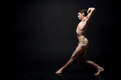 Inventive young man dancing in the black colored room. The art of presentation. Energetic involved muscular man dancing in the dark lighted room and having a Stock Images