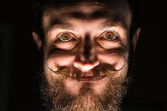 Inventor Hipster with Beard and Mustages in the Dark Room. Smiling Trickster. Inventor Hipster with Beard and Mustages in the Dark Room. Smiling Lucifer royalty free stock images