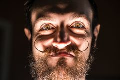 Inventor Hipster with Beard and Mustages in the Dark Room. Smiling Trickster. royalty free stock photo