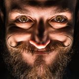 Inventor Hipster with Beard and Mustages in the Dark Room. Smiling Trickster. stock photography