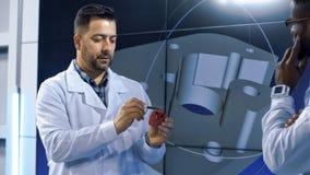 Inventores que exploram o modelo impresso 3-D do artigo fotos de stock