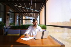 Inventory strategist working with laptop at cafe table. Royalty Free Stock Images