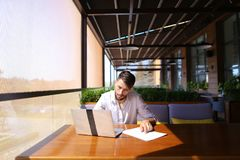 Inventory strategist working with laptop at cafe table. Stock Images