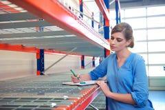 Inventário da escrita do trabalhador fêmea no armazém do depósito da entrega Fotografia de Stock Royalty Free