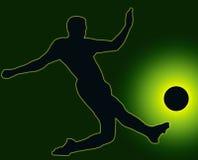 Inverdica il calciatore della siluetta che dà dei calci alla sfera Fotografia Stock
