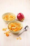 Inverdica le ciotole di fiocchi di mais croccanti per la prima colazione con la mela su w Immagini Stock