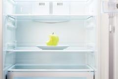 Inverdisca la mela pungente sul piatto bianco in frigorifero vuoto aperto Immagine Stock