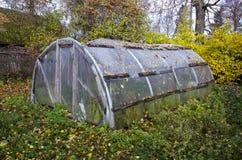 Invernadero plástico primitivo viejo en jardín de la granja del otoño imagen de archivo