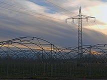 Invernaderos bajo líneas de alto voltaje por la tarde del otoño imagenes de archivo