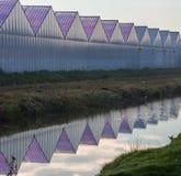 Invernaderos para la horticultura con la hierba, el cielo, la zanja y la reflexión en agua foto de archivo
