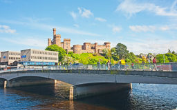 Inverness Castle alongside modern building. Historic Inverness Castle with towers and turrets beside river Ness side by side with modern concrete buildings Stock Photos